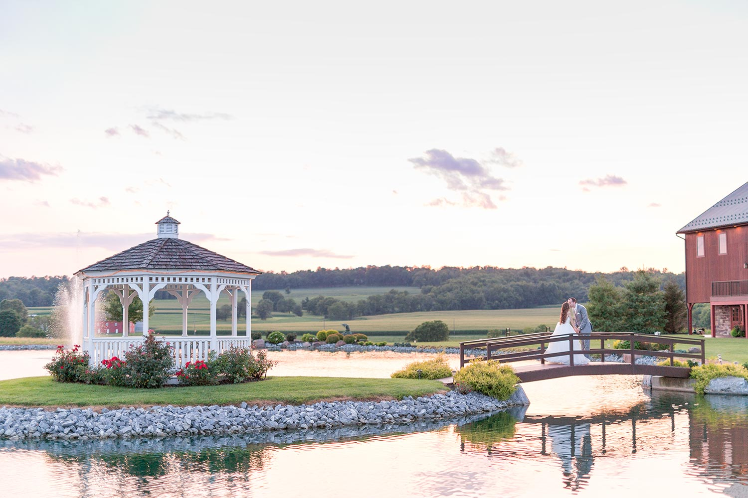 Bride and groom kissing on bridge in pond at Harvest View Barn
