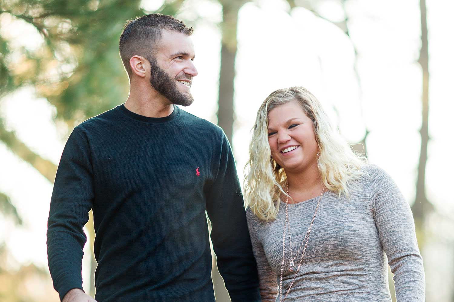 Couple laughing together while walking hand in hand at Grings Mill