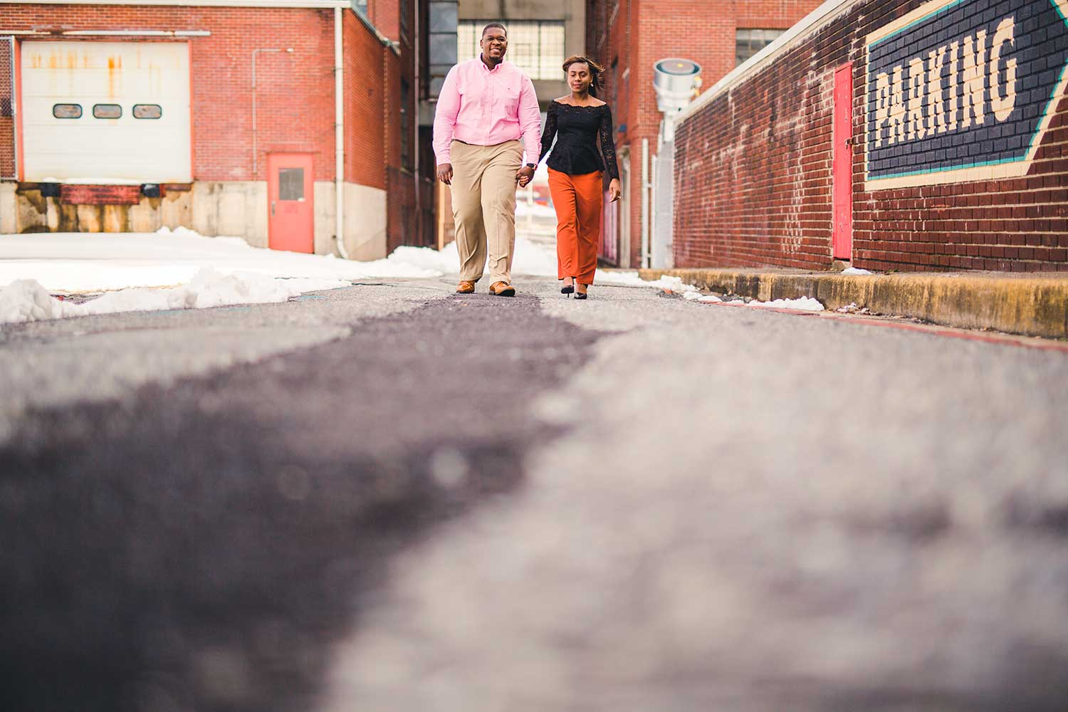 Couple walks down industrial looking alley at Goggle Works
