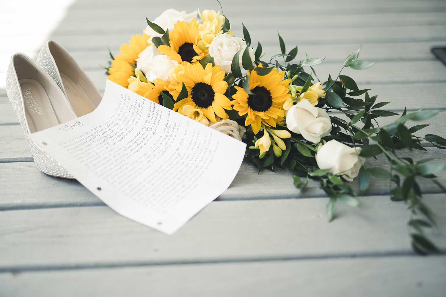 Detail shot of shoes, bouquet, and wedding vows