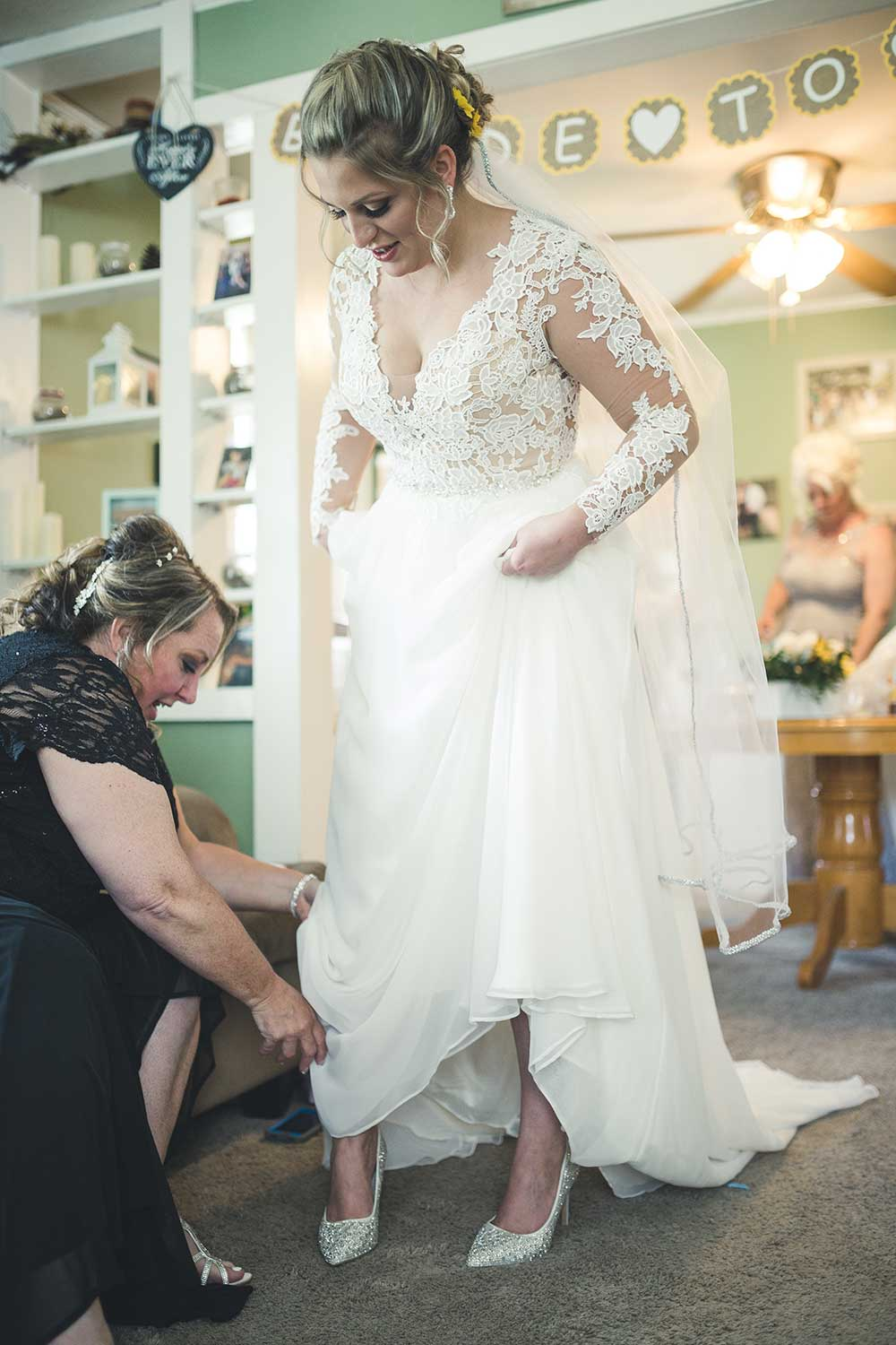 Mother of the bride helping her into her shoes