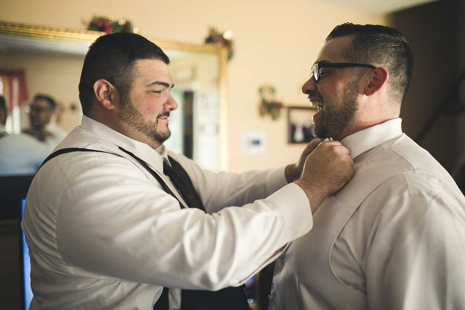 Best man adjusting the grooms bowtie