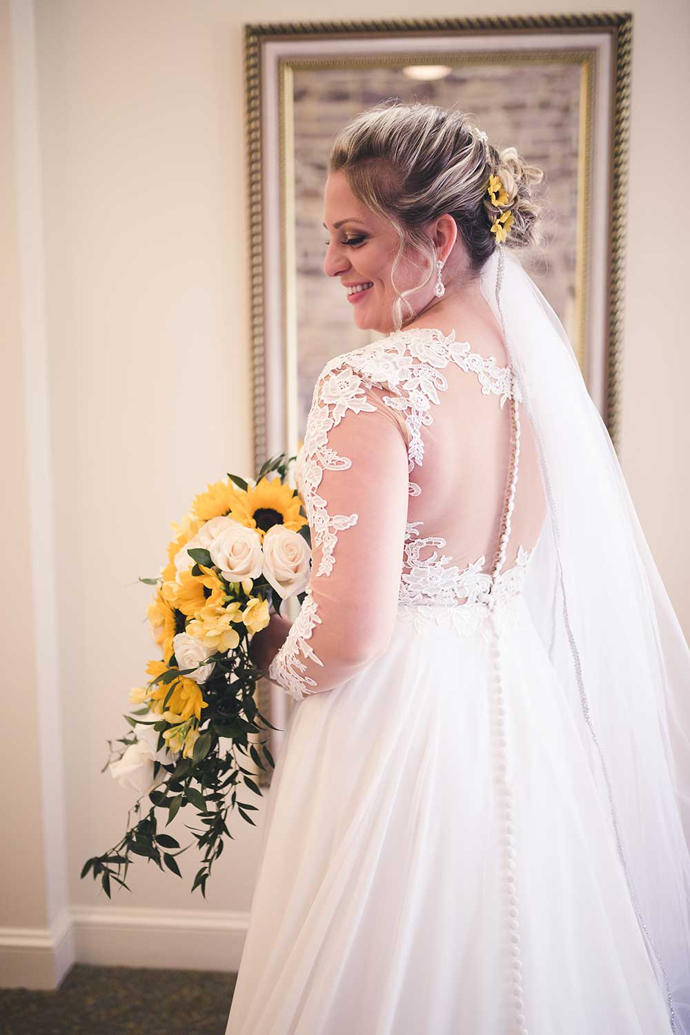 Bride in her dress with sunflower bouquet