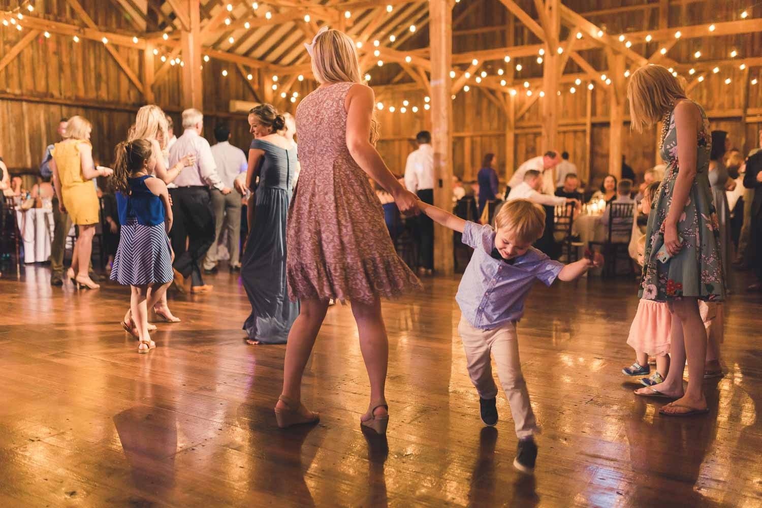Child dancing around his mother at wedding reception