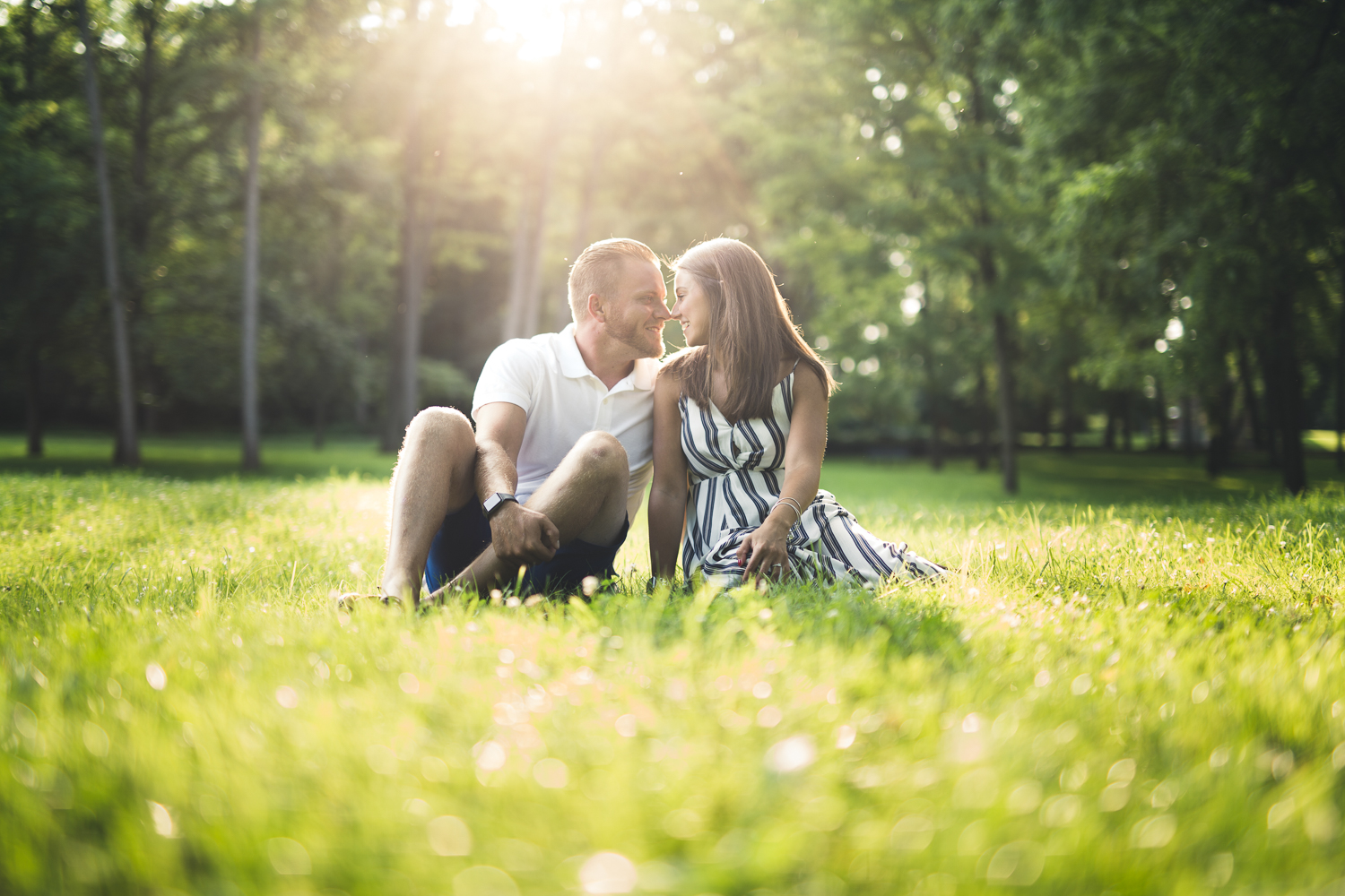 Allentown Engagement photographer captures couple sitting in field together at sunset