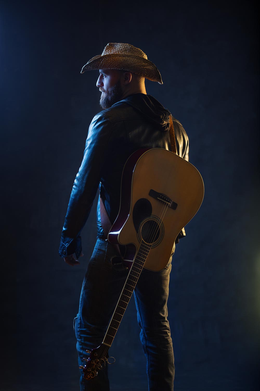 Musician poses with guitar in dramatic colored light