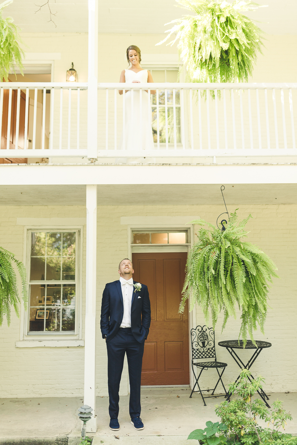 Groom looking up at bride on balcony