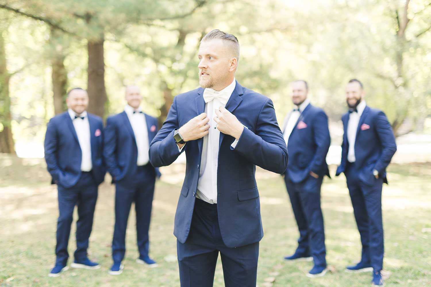 Portrait of Groom with groomsmen in background