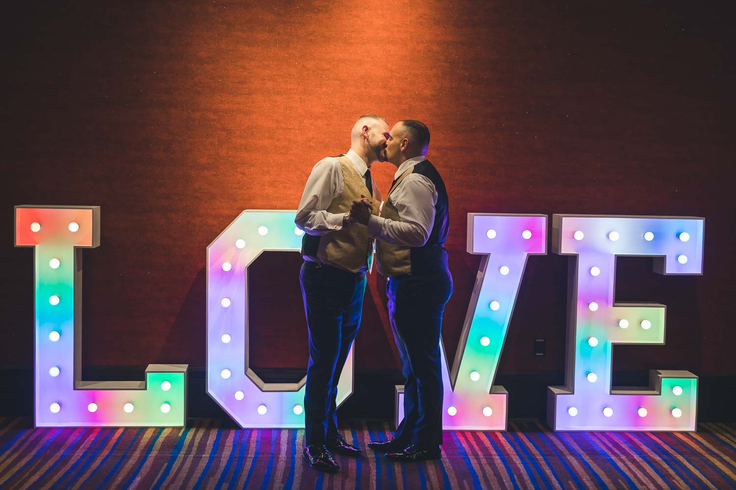 Couple kissing in front of LOVE sign