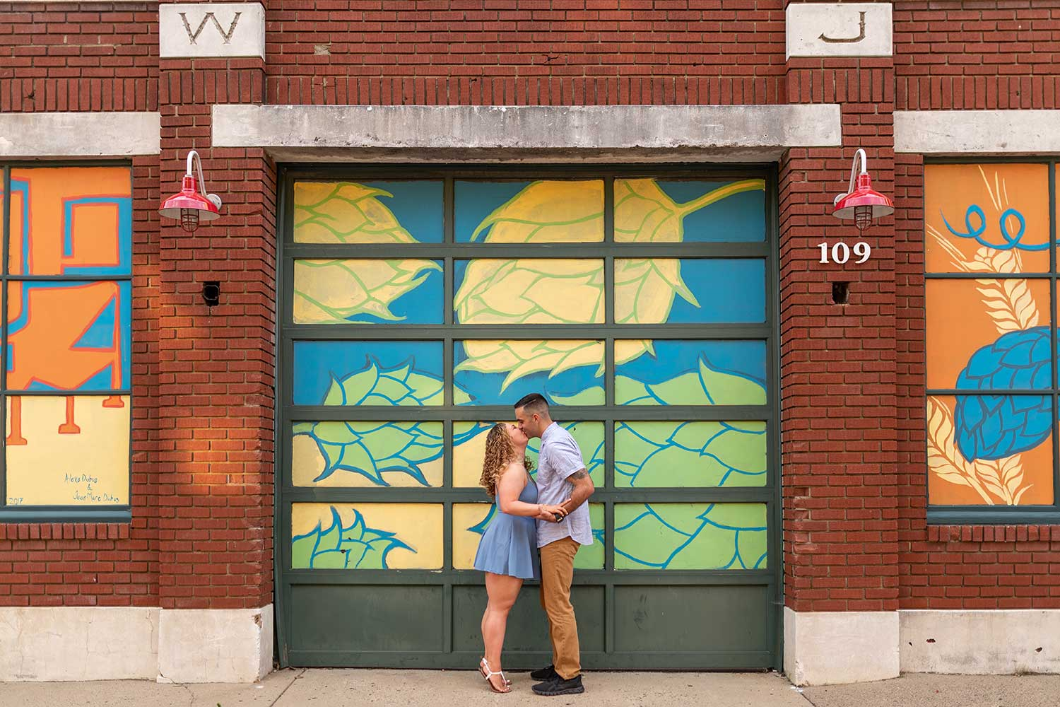 Engagement photos in front of brewery mural in Bristol PA