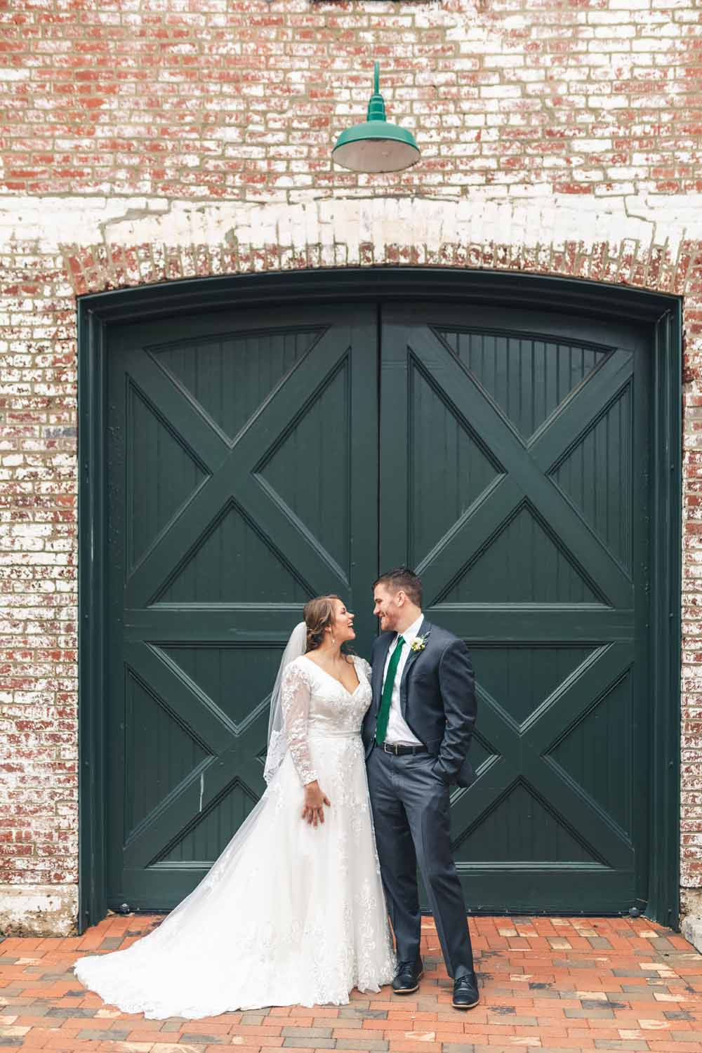 Bride and groom looking into each others eyes in front of brick wall with green door