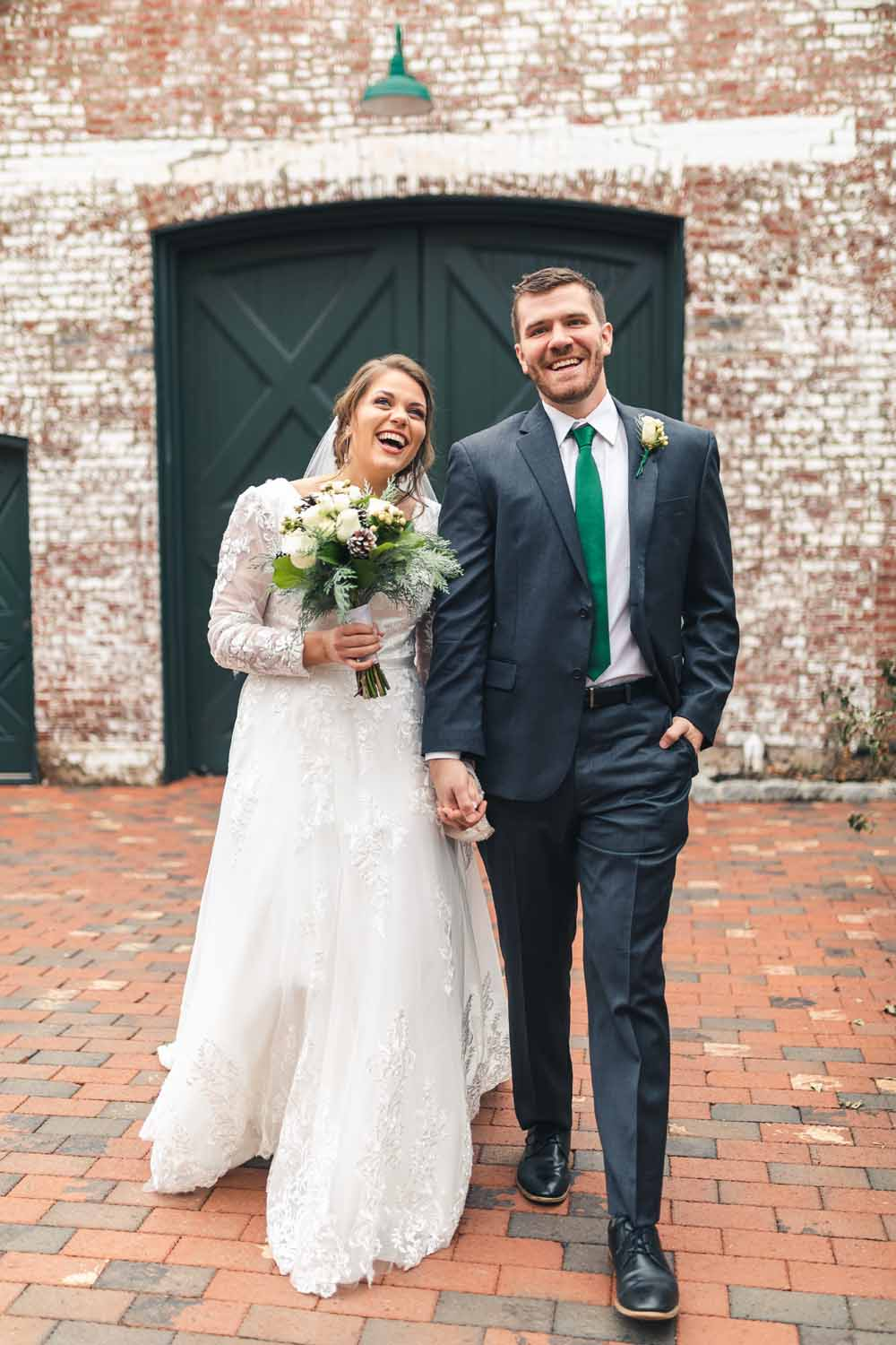 Bride and groom hold hands and walk together, laughing, after first look