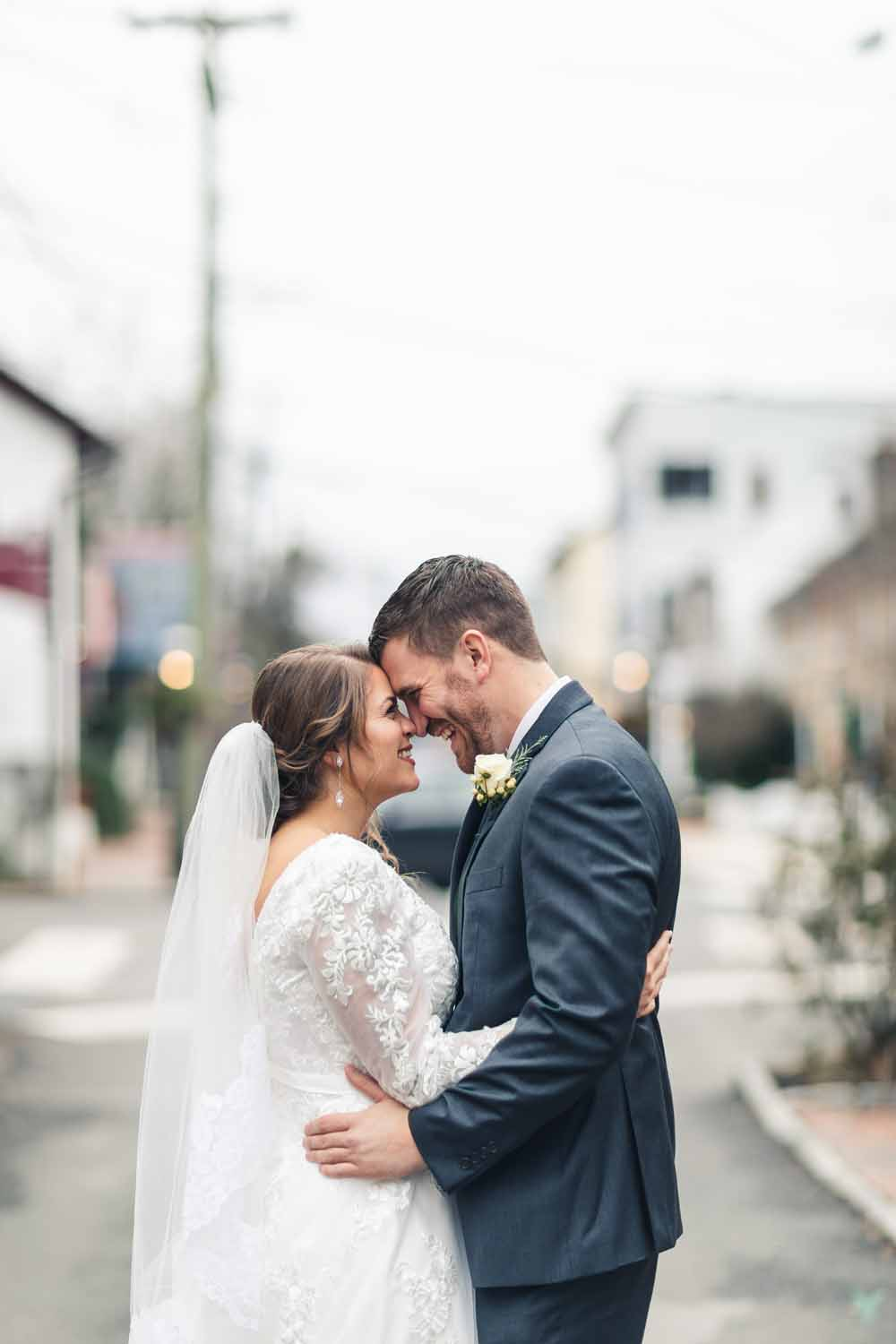 Bride and groom laughing while nose kissing