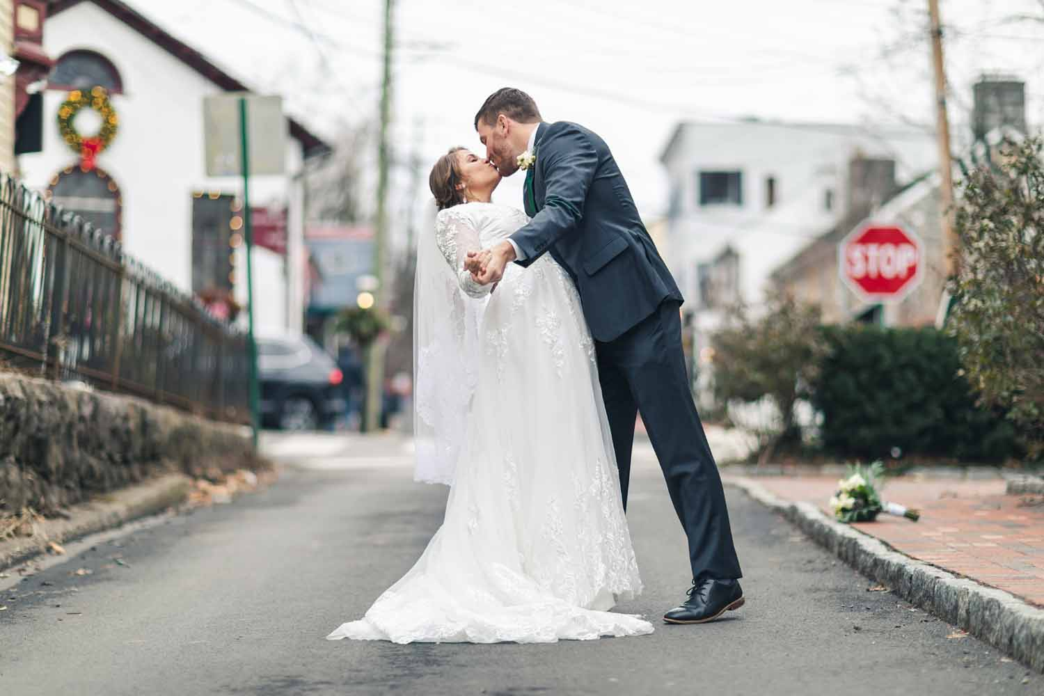 Grooms dips and kisses bride in a street on New Hope