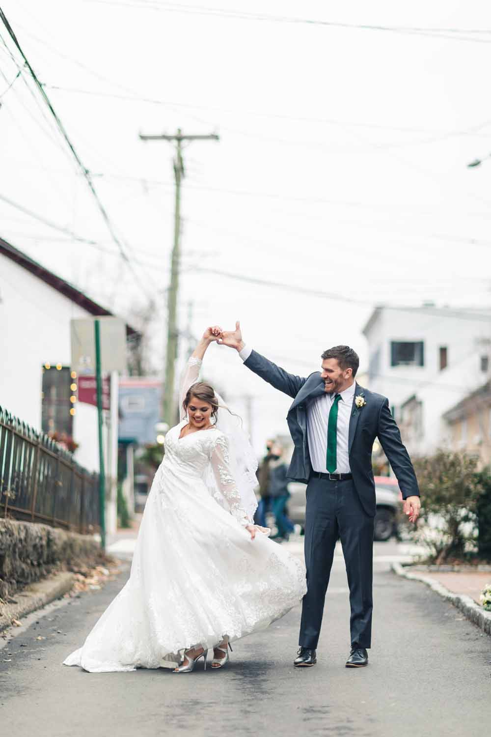 Groom spins bride in front of Carriage House of New Hope