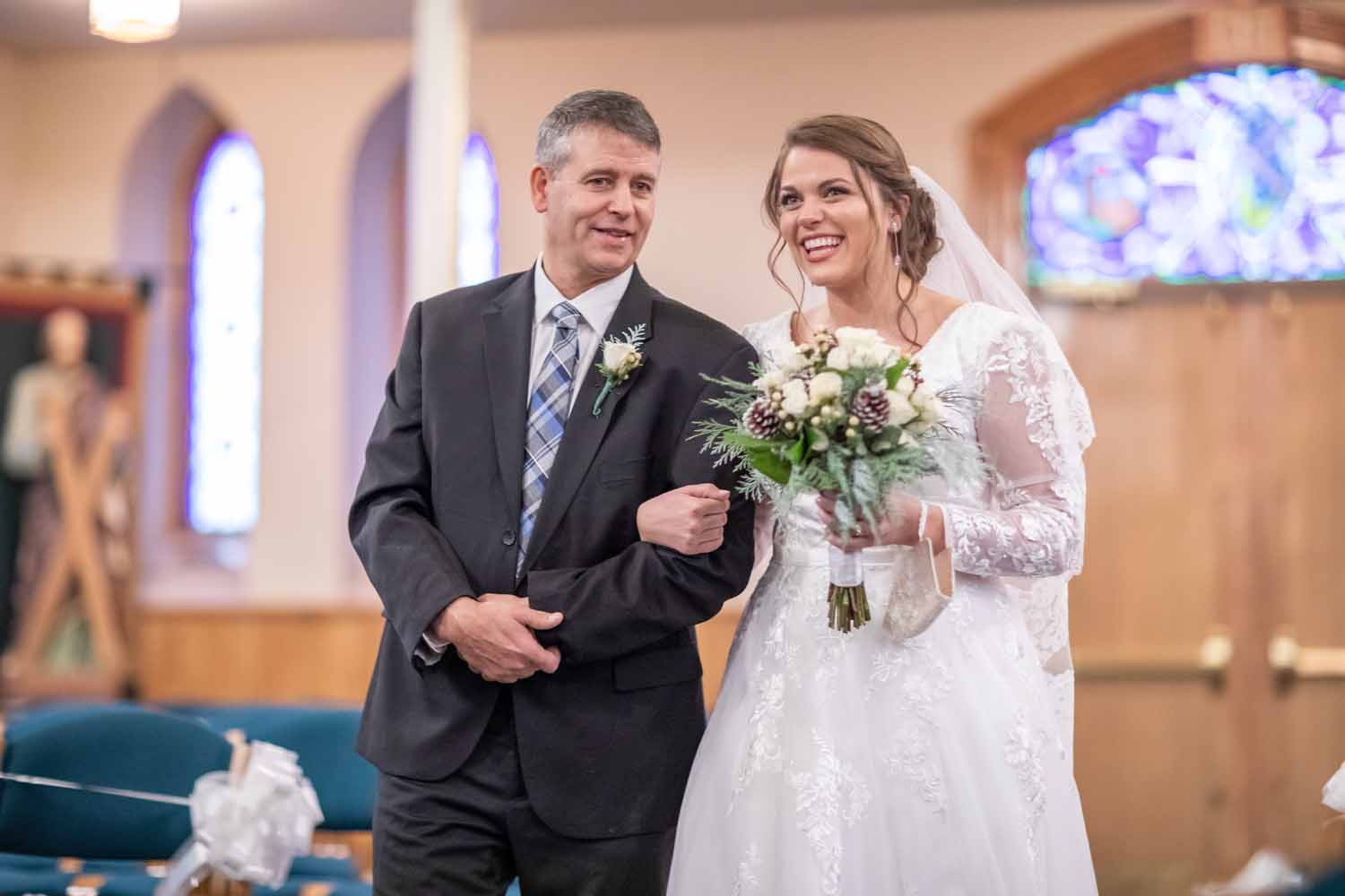 Bride and father walk down aisle together