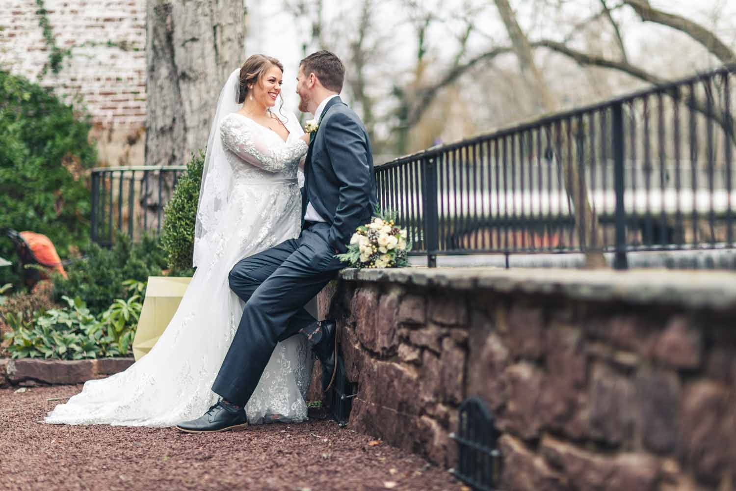 Groom leans against stone wall facing his bride
