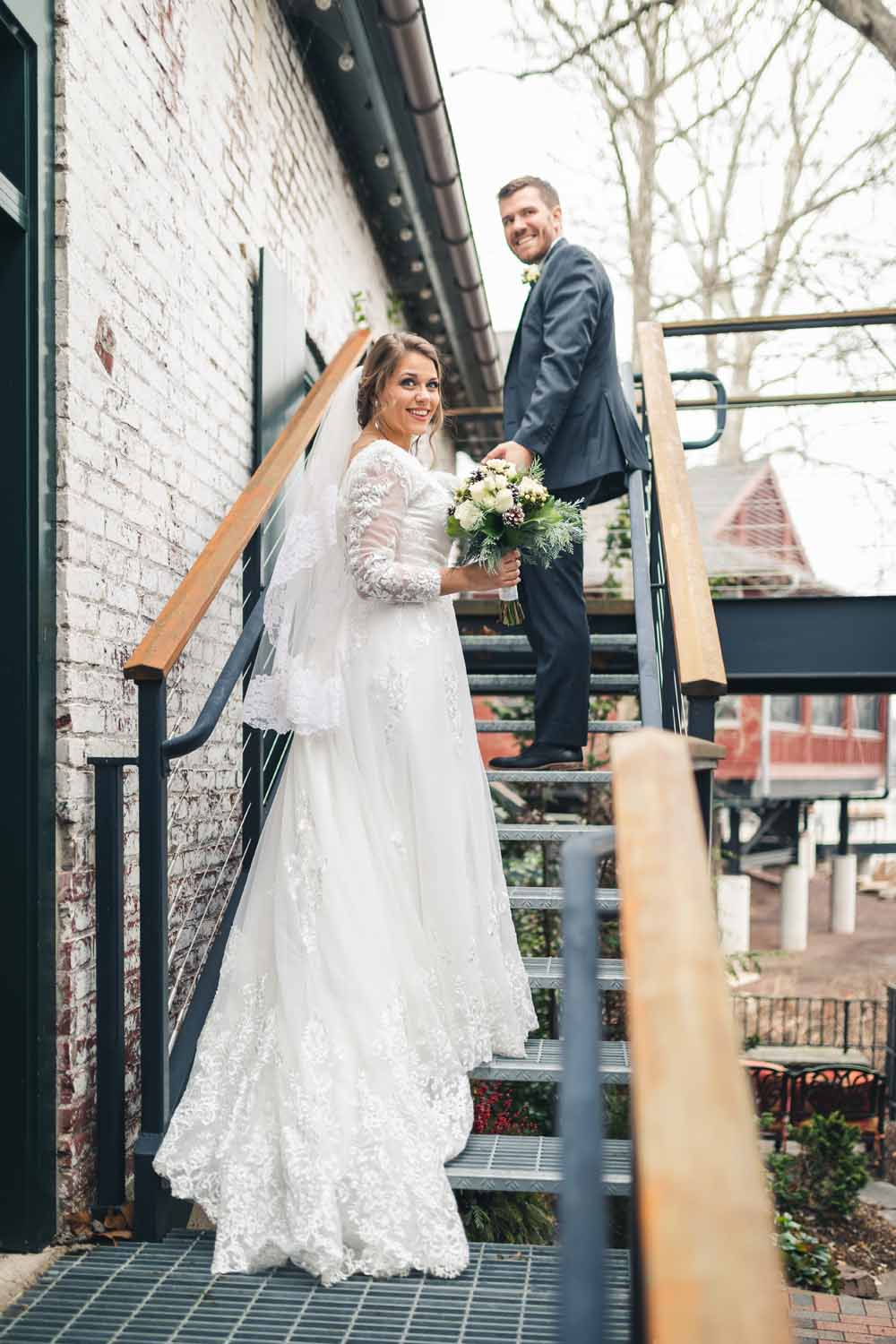 Bride and groom pose on stairs at New Hope Carriage House