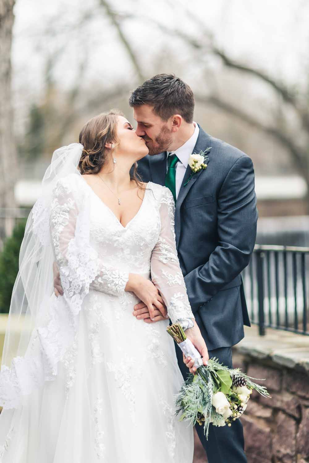 Bride and groom kiss outside at Carriage House
