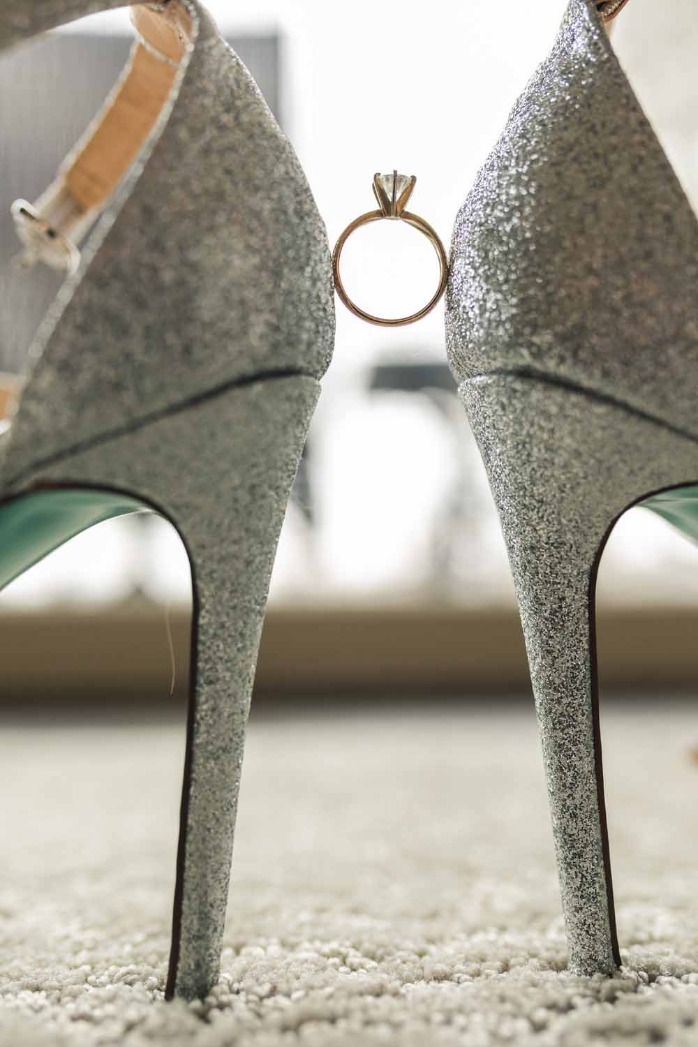 Wedding ring held up by brides shoes