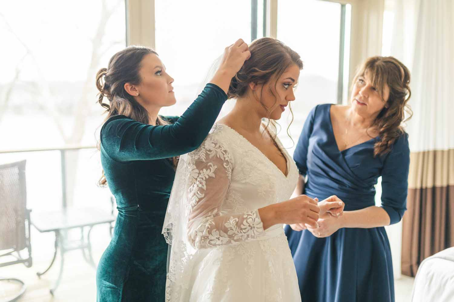 Bridesmaid and mother putting veil in brides hair