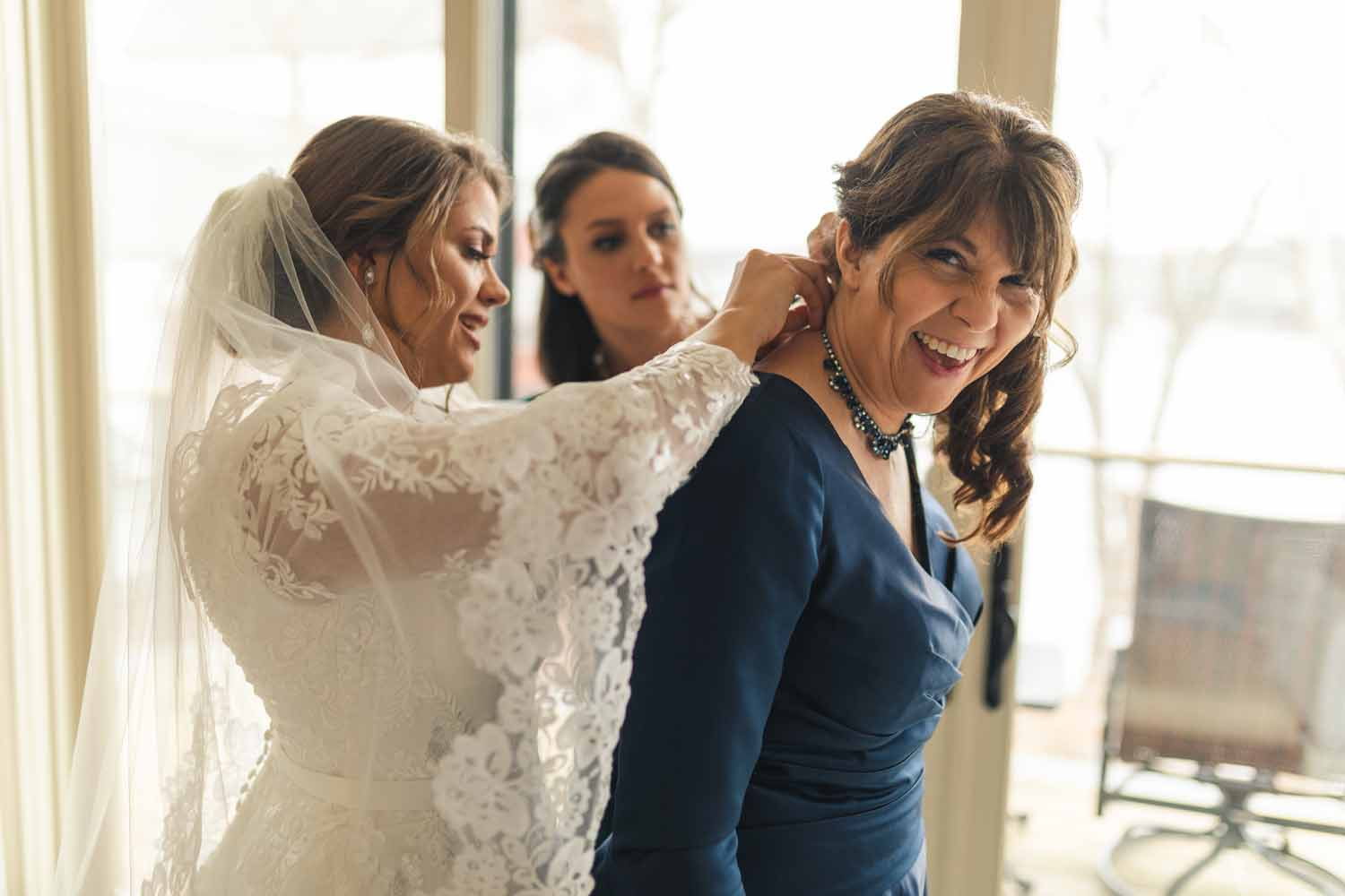 Bride putting necklace on mother before wedding