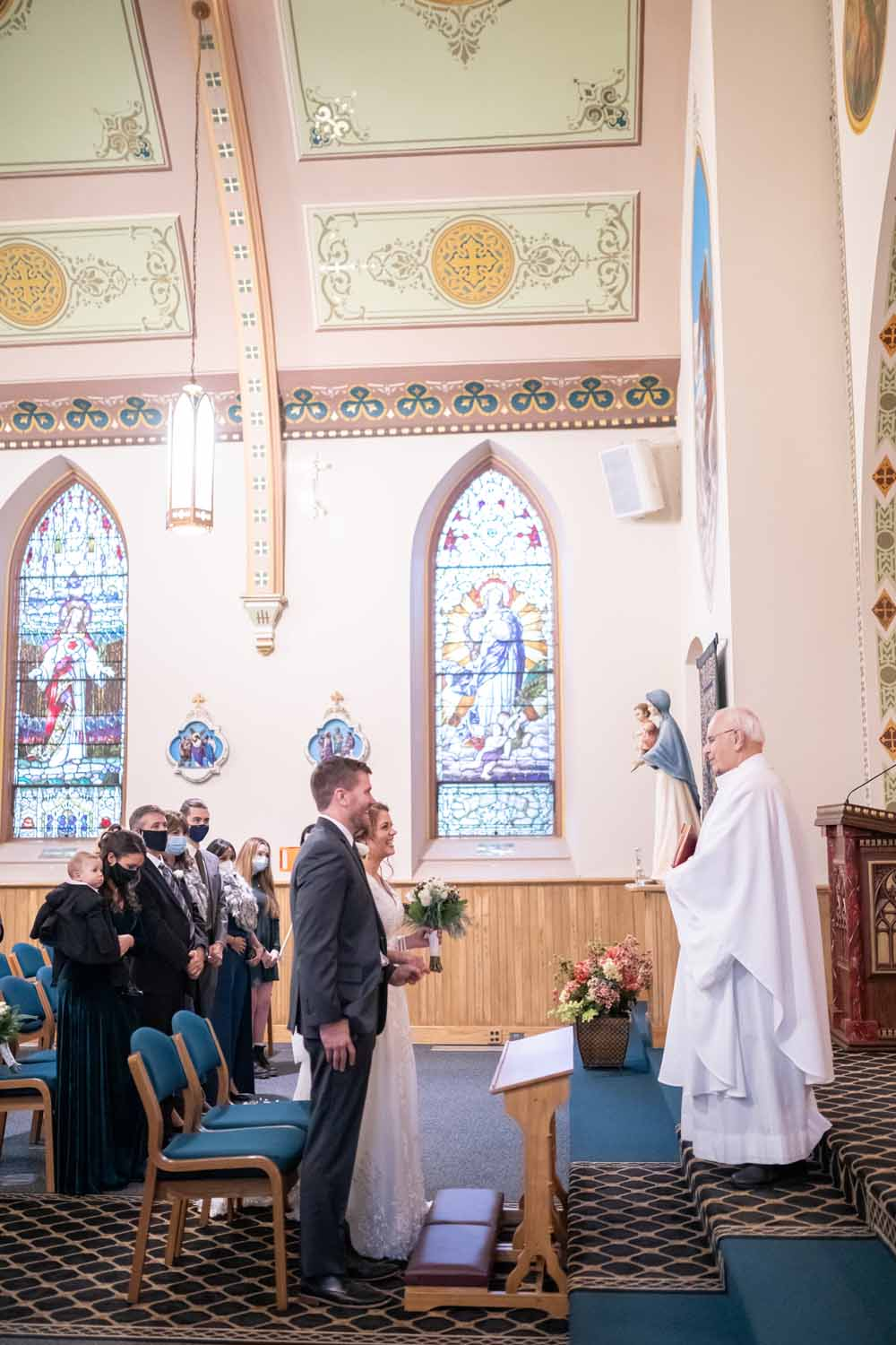 Couple laugh with Monseigneur during Catholic wedding