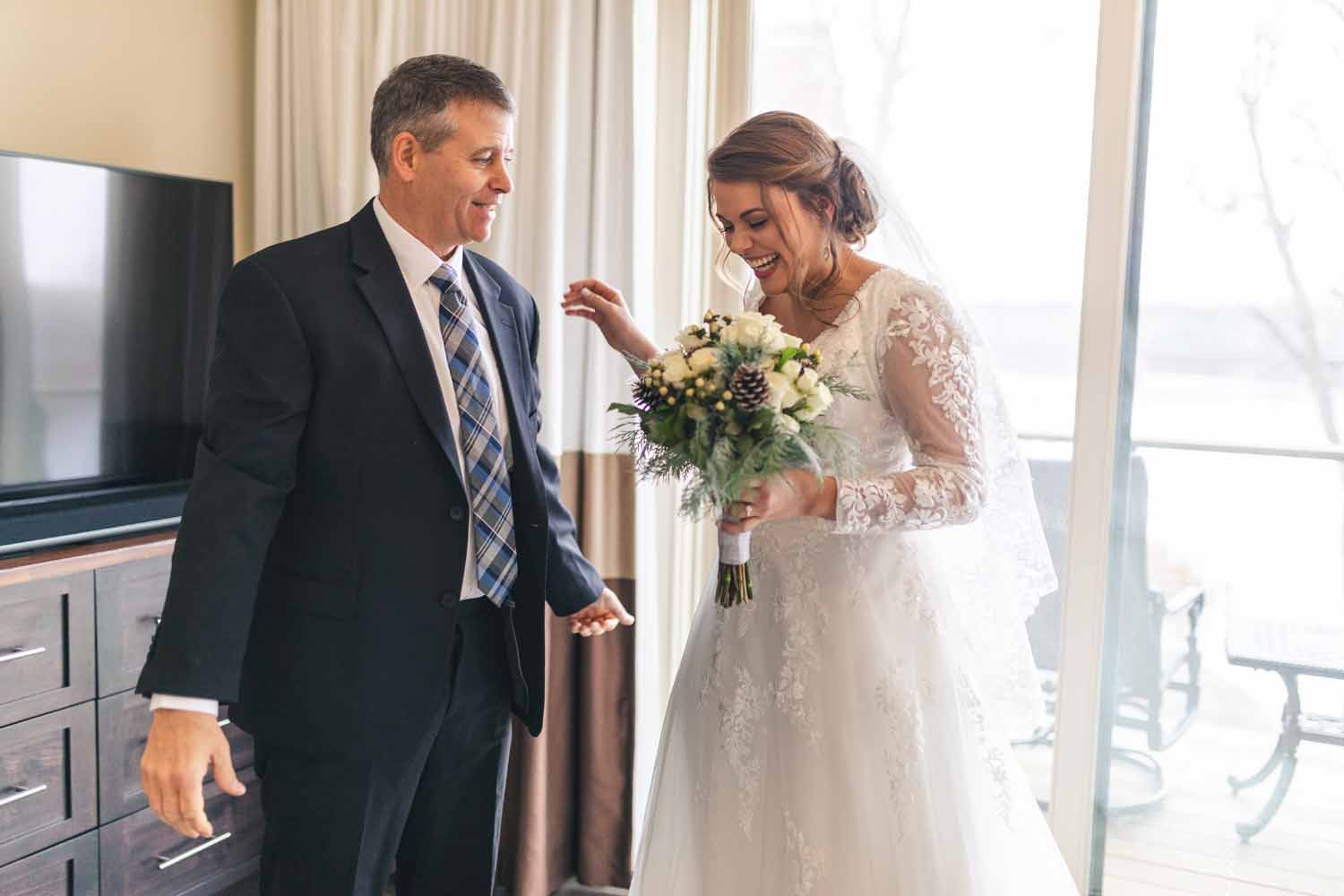 Bride and father laughing together