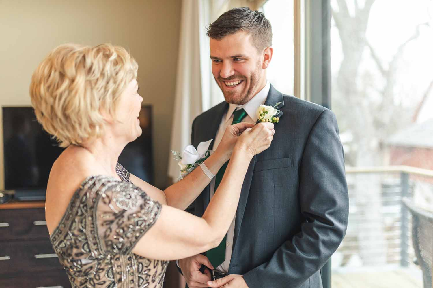 Mother of the groom places boutonniere on lapel