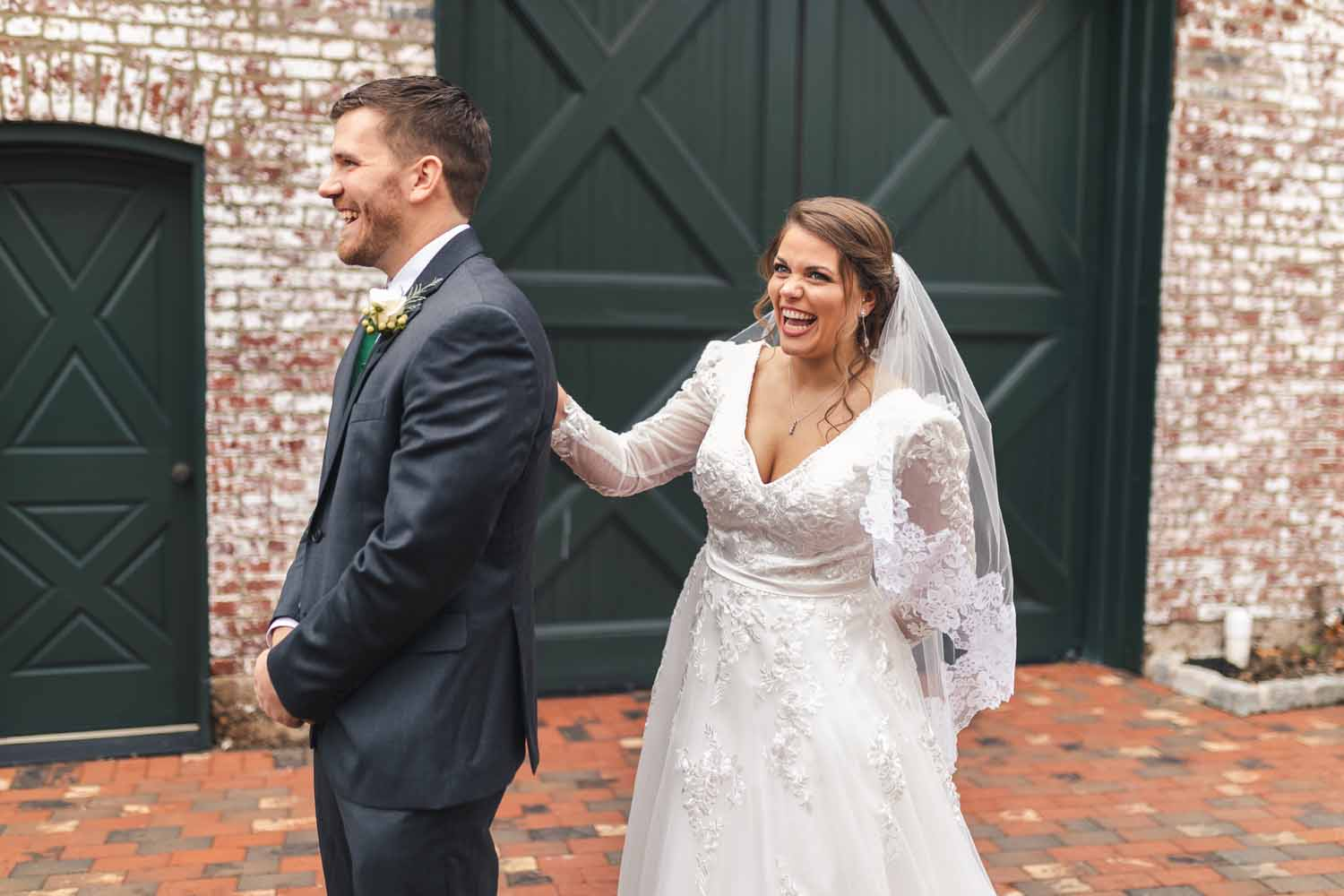 Bride laughing right before groom turns around to see bride for first time