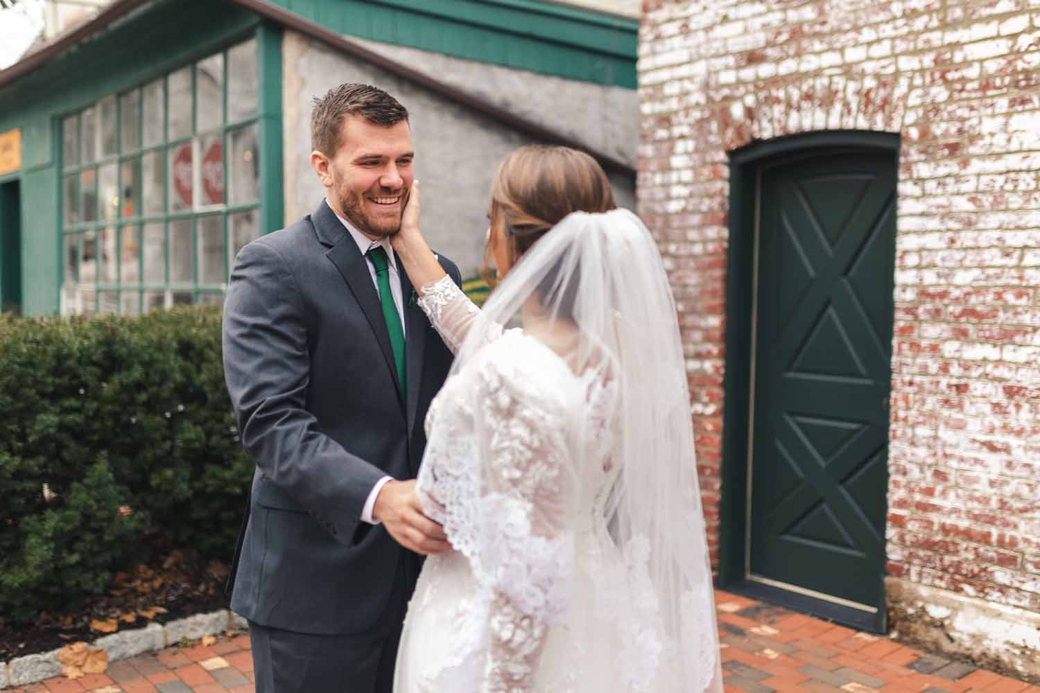 Bride places hand on grooms cheek during first look