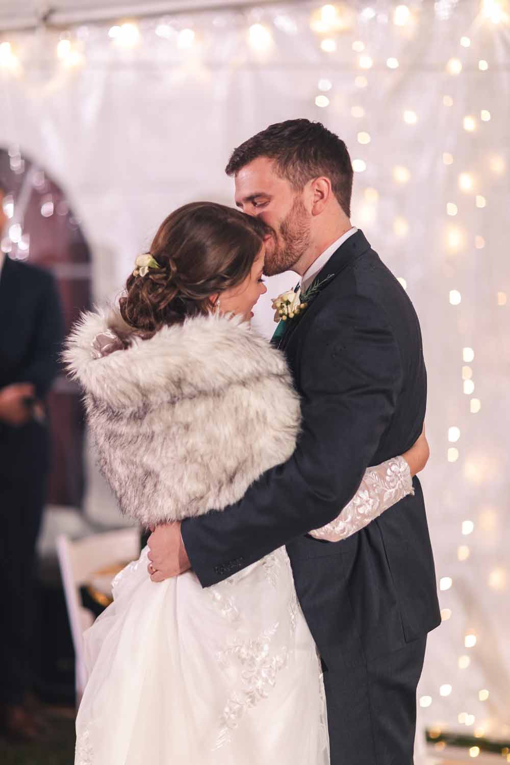 Groom kissing bride on forehead during first dance