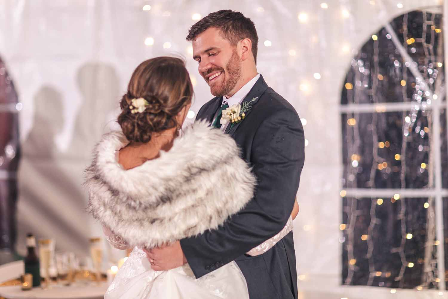 Groom looking into brides eyes while dancing at reception