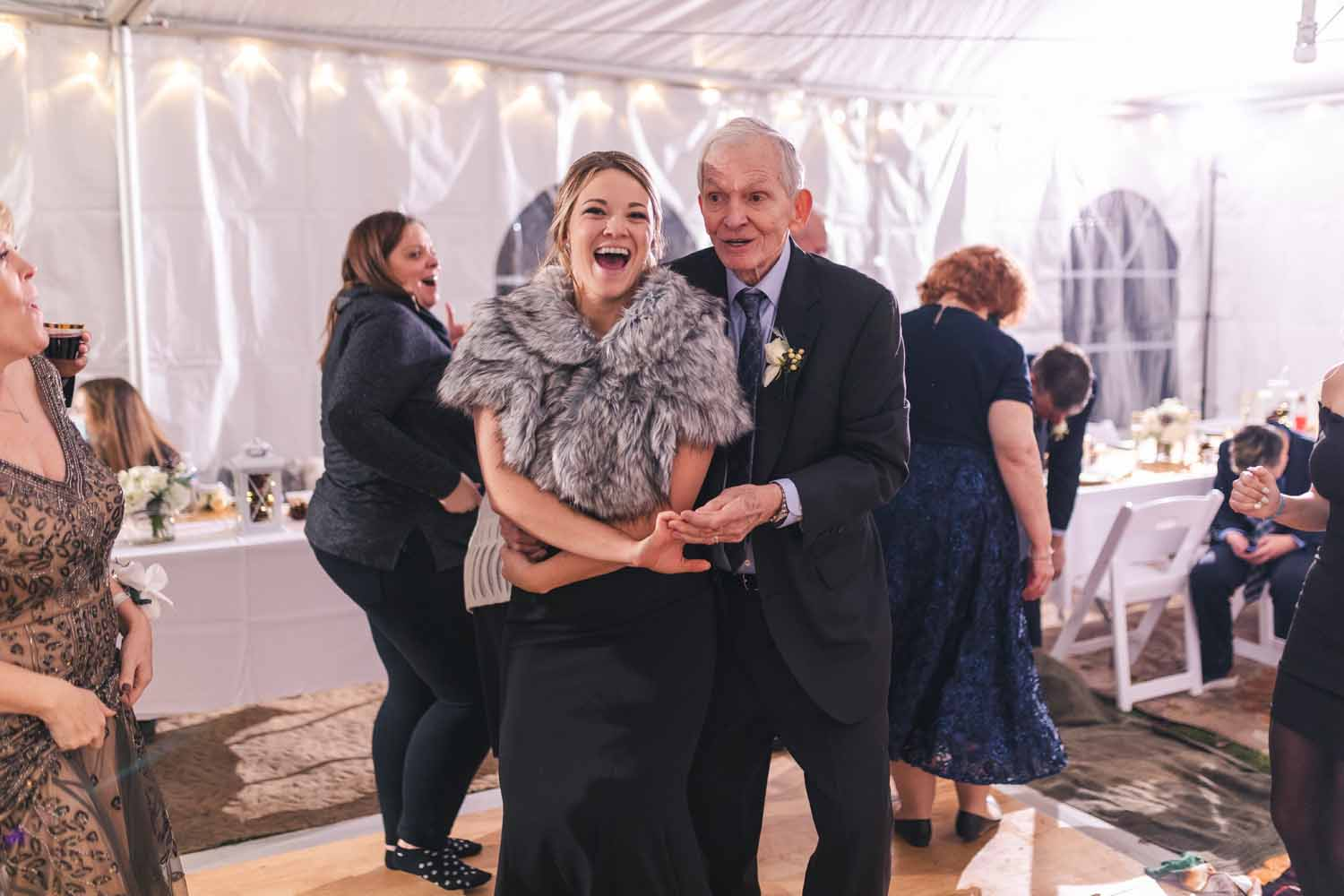 Grandfather dancing with granddaughter at wedding reception