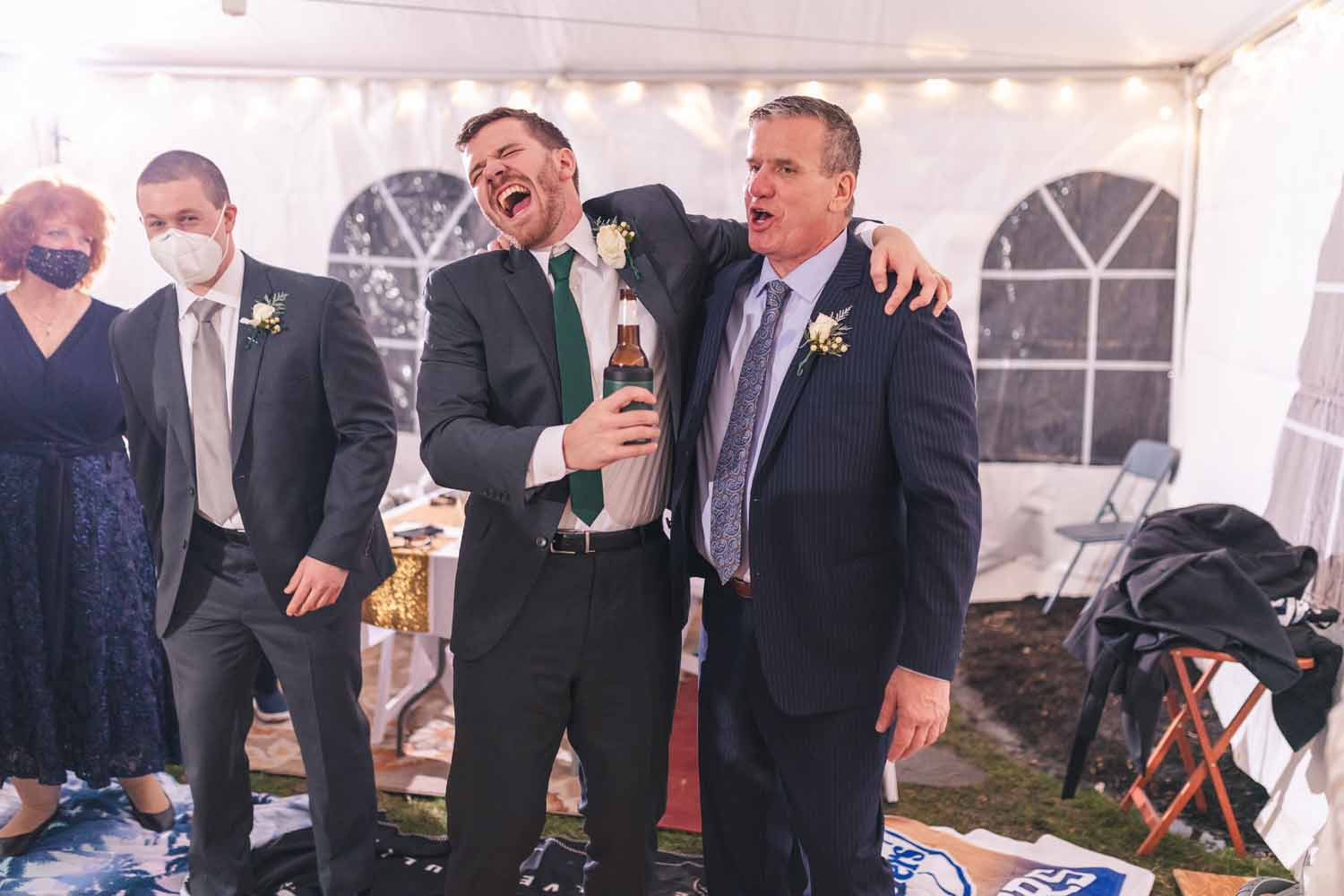 Groom using beer bottle as microphone during reception