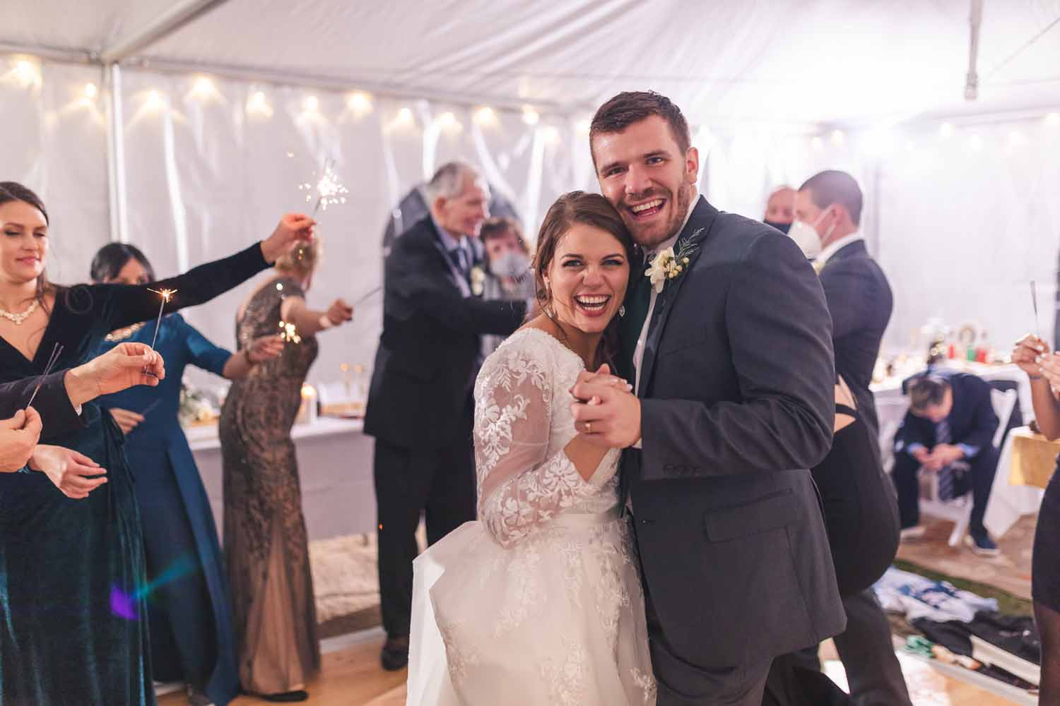 Couple dancing with guests holding sparklers