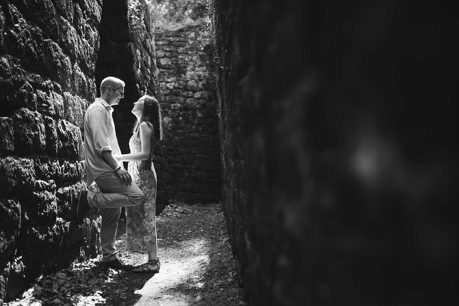 Hopewell Furnace Couples Portraits with couple being backlit by bright sunlight in a stone hallway