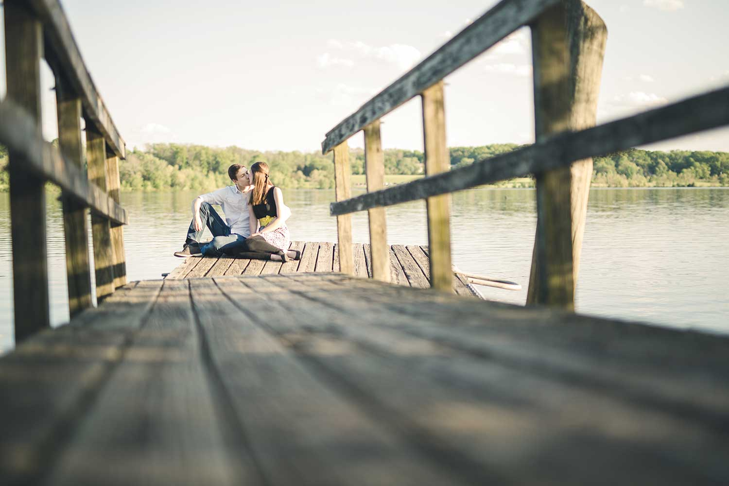 Peace Valley Park Engagement Photos with couple sitting together and kissing on a fishing dock