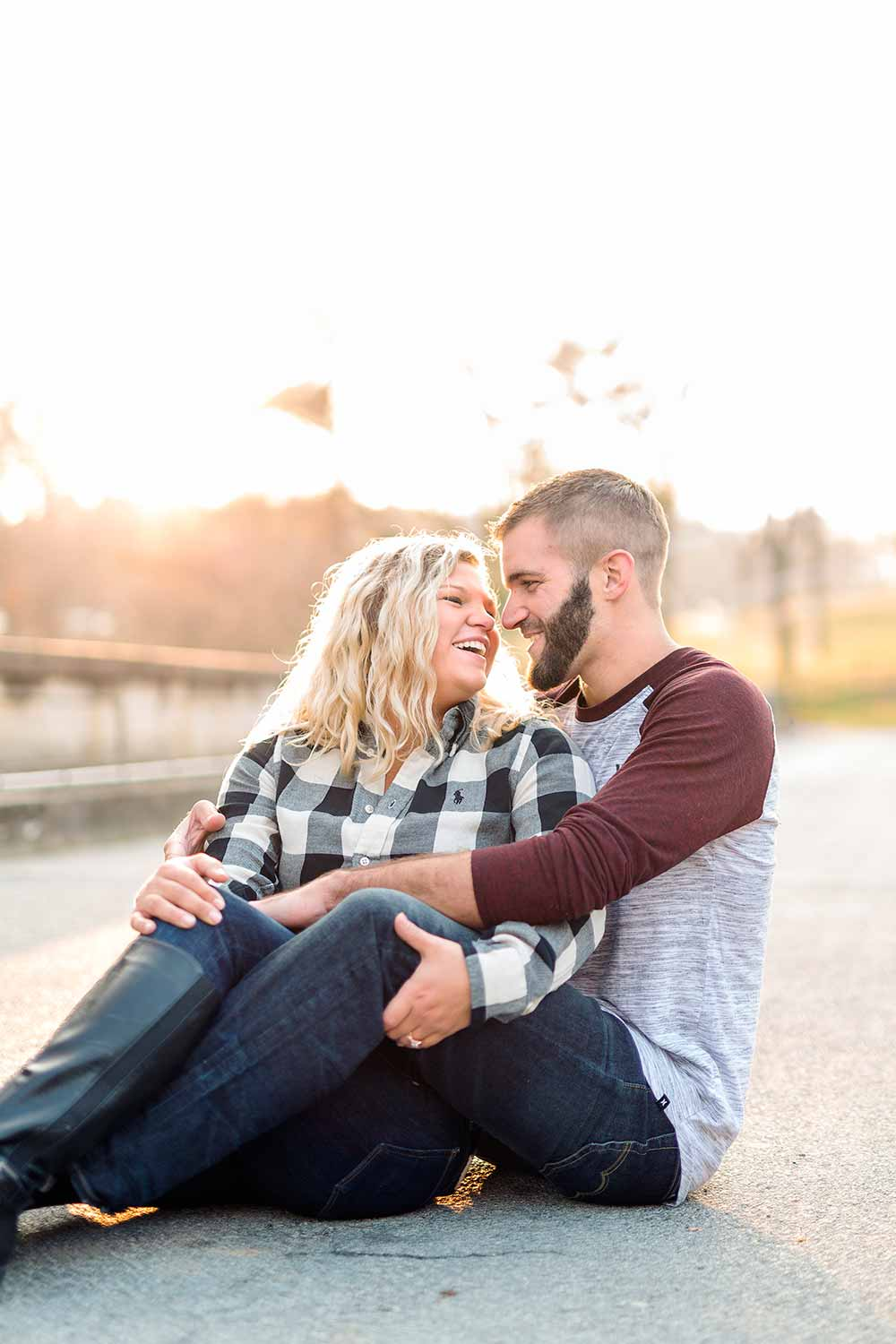 Yardley Engagement Photo with couple sitting on bridge and laughing together